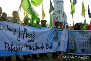 Pelajar dari berbagai sekolah yang tergabung dalam Pelajar Islam Indonesia (PII) Aceh membentangkan spanduk saat berorasi di Bundaran Simpang Lima, Banda Aceh, Senin (13/1).